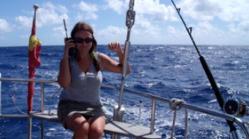Elena en un barco hablando por teléfono satélite